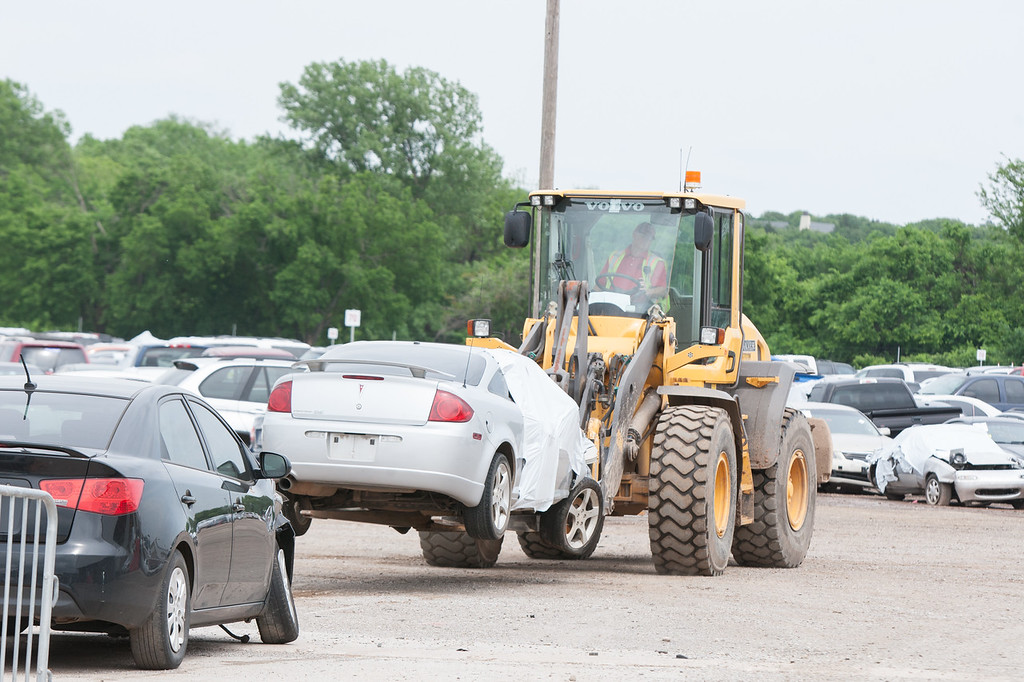 A loader moves a car at Insurance Auto Auctions in northeast Oklahoma City, OK.