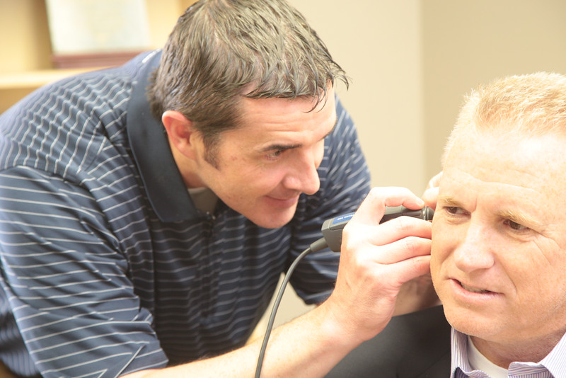 Jace Wolfe worinking with a patient's cochlear implant at Hearts for Hearing in Oklahoma City.