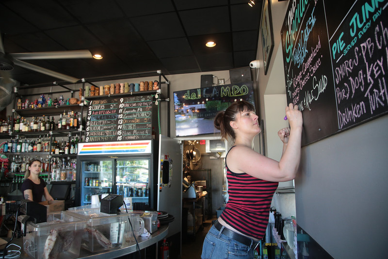 Charmian Conrad writes the day's specials on a chalkboard at Pump Bar in Oklahona City.