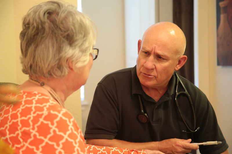 Dr. Scott Dellinger talks with a patiens at Willowood Senior Living Center in Mustang, OK.