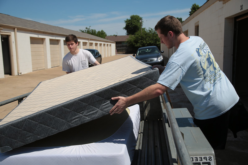 Ben Dougherty and Riley Guy with Bellhops Movers unload a storage unit in Norman, OK.