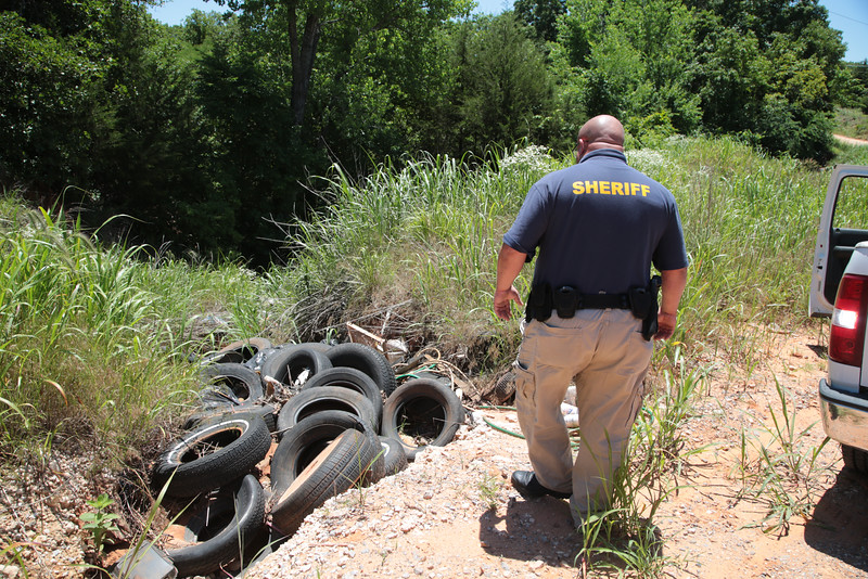 Deputy Philip Bennett inspects illigal trash dumping at Capt Creek Toad and Wilshire Drive in southwest Lincoln County, OK.