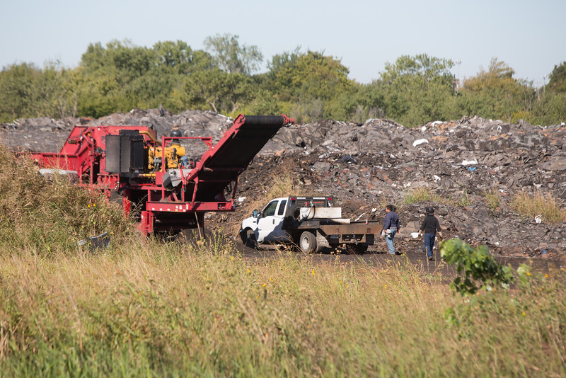 Shredding of roof shingles at an illegal dump under the contol of Oklahom Department of Enviromental Quality.