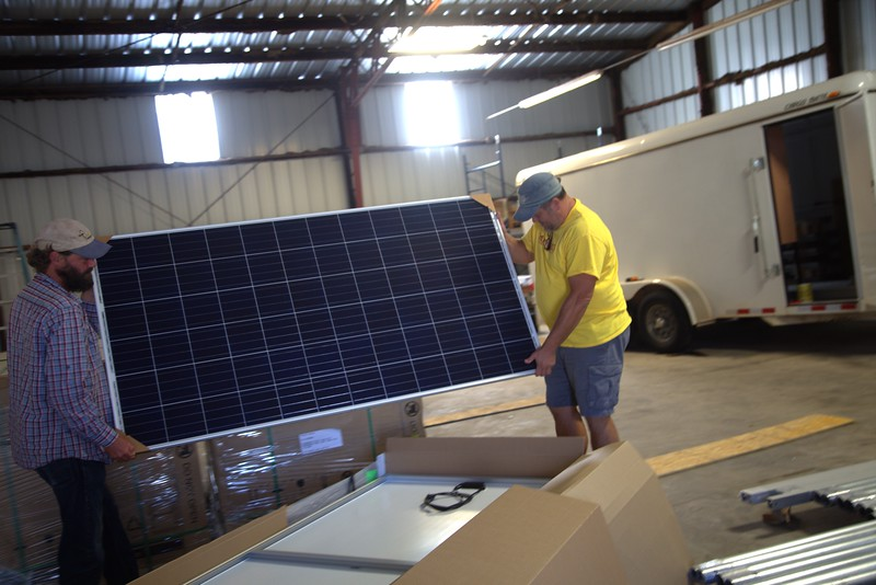 Tod Hanley and Steve Wilkie unpack a solar panel at Delta Energy and Design in Norman, OK.