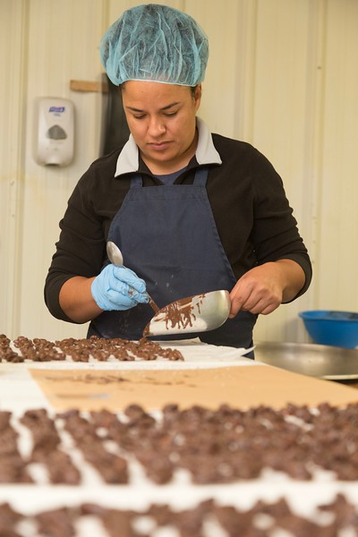 Chocolate and sea salt covered almond clusters being separated at Woody Candy Company in Oklahoma City.