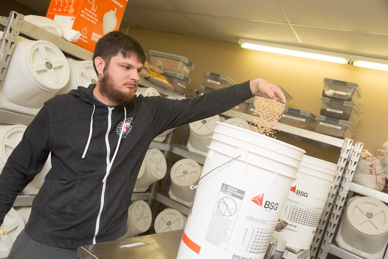 Manager Evan Smith measures grain at Learn to Brew located at 6900 N May in Oklahoma City, OK.