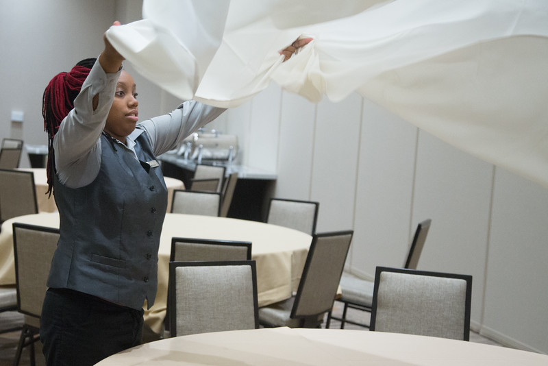 Shekeyra Goodman setting a table in an event room at Embassy Suites Downtown located at 741 North Phillips Avenue in Oklahoma City, OK.