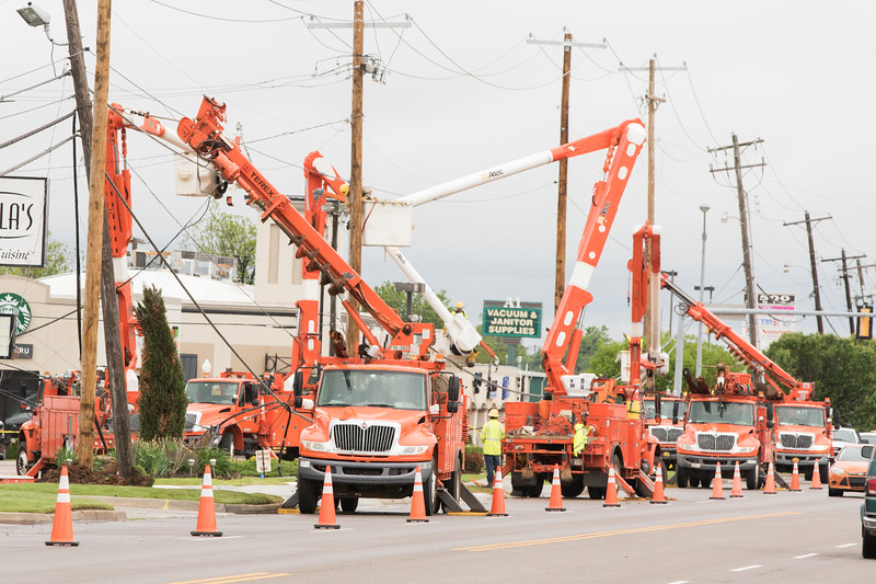 Crews from OGE work to restore power after high a storm blew over a row of utility poles along May Ave. just south of Grand Blvd in Oklahoma City.