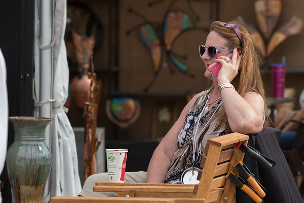 A woman using her phone at the Oklahoma City Festival of the Art held at Centinial Park.