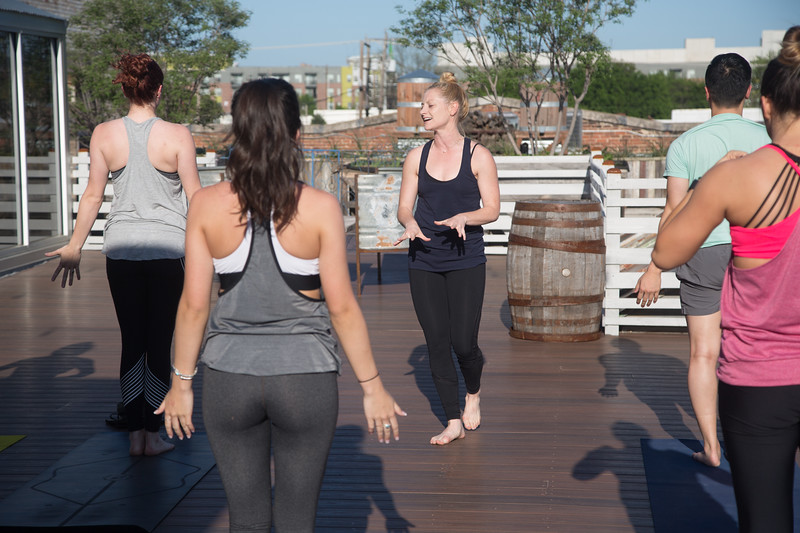 Marideth Van Sant instructing a pop-up yoga session on the roof top of Plenty Merchintile located at 1006 N Hudson Ave. in Oklahoma City.