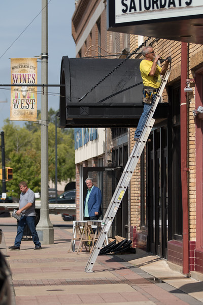 An electrition wires a new light fixture outside of a new resturaunt in the Stackyard District of Oklahoma City at Agnew Rd and Exchange Ave.