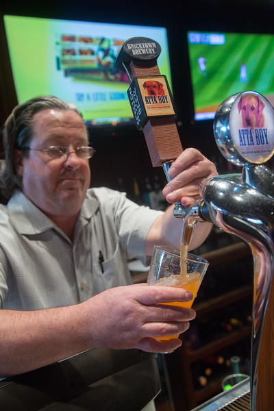 Charles Stout pours an Atta Boy orange hard soda at Bricktown Brewery located at 1 N Oklahoma Ave in Oklahoma City, OK.
