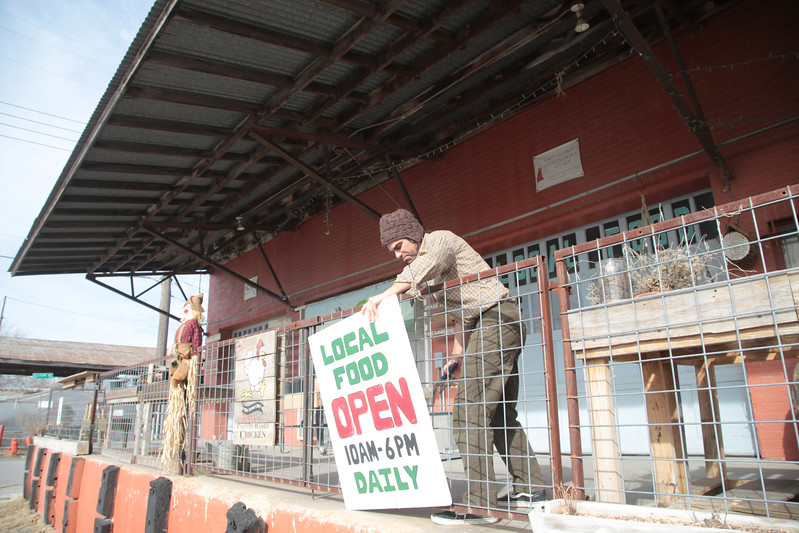 """Roy Diehl removes the """"open"""" sign from in front of Urben Agrarian located at 1235 SW 2nd Street in Oklahoma City."""