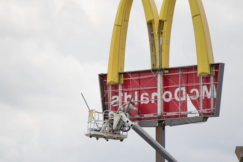 A man repairs a wind damaged sign at McDonald's located at 1004 W Sheridan Ave in Oklahoma City, OK.