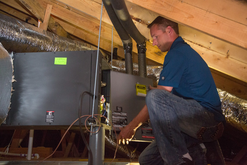 Chris Ellis, with Comfort Works, working with a new geothermal heat exchange unit installed in a new house in Yukon, OK.