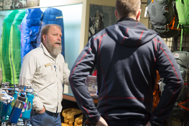 Tom Adams, general manager of Backwoods located at 12325 N May in Oklahoma City, helps a customer choose a backpack for hiking.