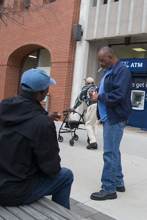 A passerby shares a cigerette with a man in downtown Oklahoma CIty, OK.