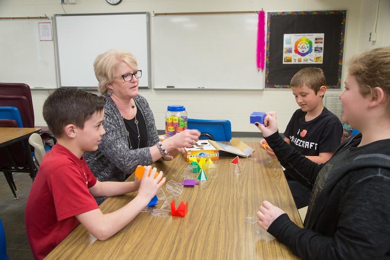 Math teacher Lisa Harris worth with students and geometric shapes.