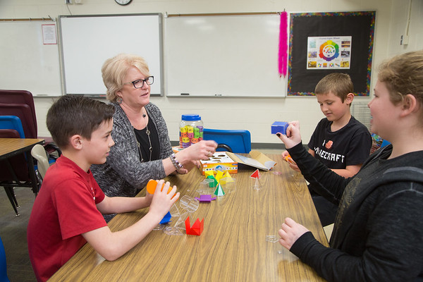 Math teacher Lisa Harris worth with students and geometric shapes.