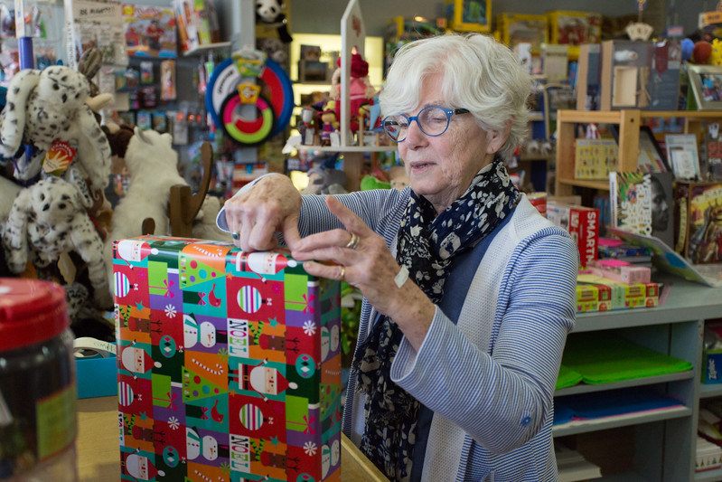 Patti Tepper-Rasmussen helds a customer with a Christmas gist at Learning Tree located at 7638 N Western Ave in Oklahoma City.