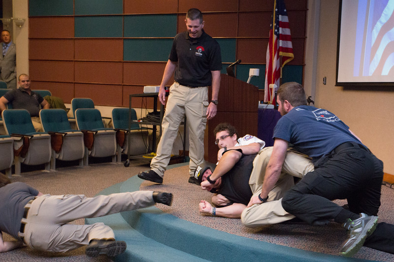 Three volunteers from the audience tackle Tim Smith, who acted as an armed gunman for an active shooter training workshop he and Tony Riddles led at Norman Regional Hospital Friday. The Cody Conference for Mass Casualty Disaster Preparedness was a two-day event focused on providing information for doctors, nurses, firefighters, paramedics and other first responders. Photo by Brent Fuchs.