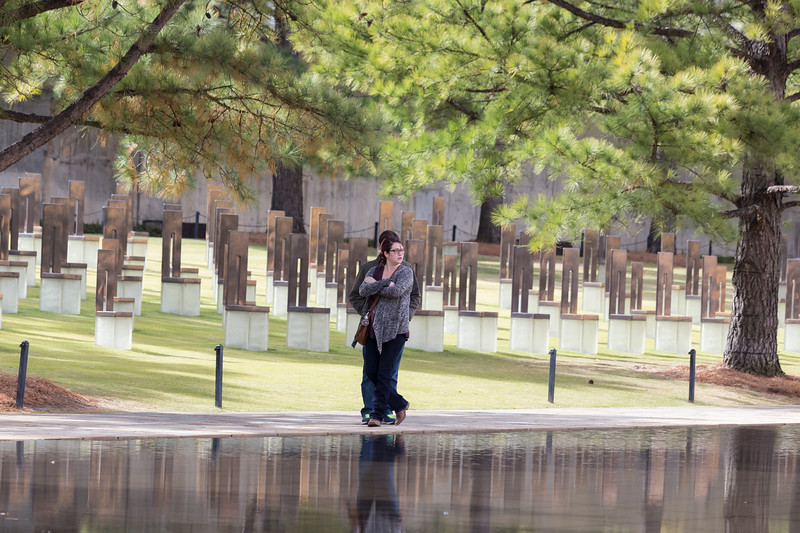 Jayla Wyatt and Adam Boyette walk along the water feature at the Oklahoma City Bombing Memorial Park on Tuesday, November 21, 2017 in Oklahoma City. (Emmy Verdin/Photographer)