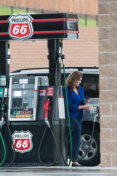 A woman getting gas at OnCue Express located at 4100 E 15th St in Edmond, OK.