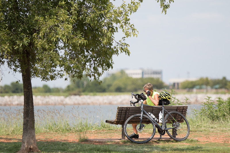 A cyclest taking a break at Lake Hefner in nowthwest Oklahoma City, OK.
