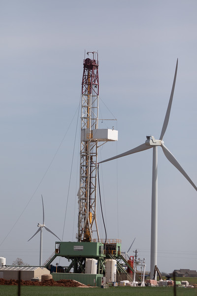 A drilling rig operated ny Newfield Energy surrounded by wind turbines in Kingfisher County, OK.