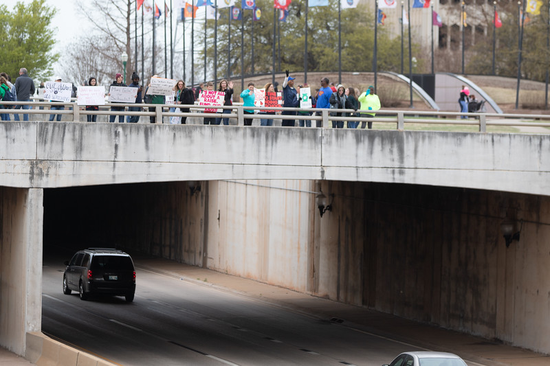 Protesters hold signs and wave at traffic on 23rd Street from a bridge on the north side of the Oklahoma State Capitol.