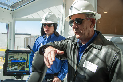 Dustin Williams, left, rig manager for Unit Drilling Company, and Allen Martin, right, operations manager for Unit Drilling, explain new features in the dog house, where the driller controls the rig.