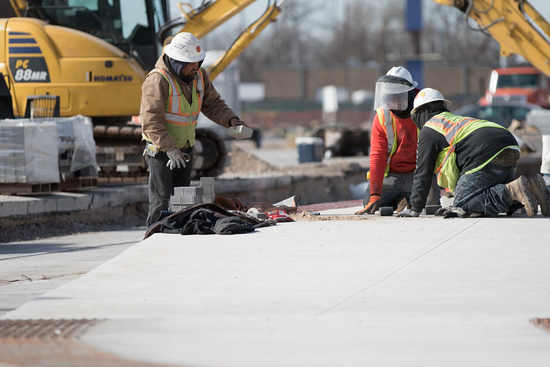 Paving stones being laid in the median of Oklahoma City's new street car near Scissortail Park.