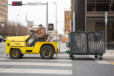 A man driving a tug pulling a dumpster through downtown Oklahoma CIty.
