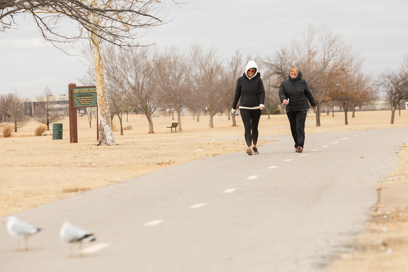 Two women walking at Lake Hefner on a windy day in Oklahoma City.