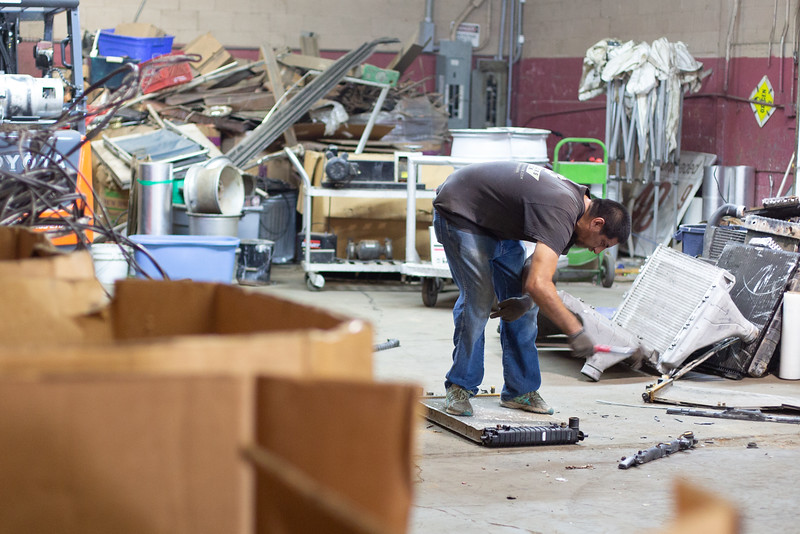 An employee removes plastic from an aluminum radiator at Recyclers of Main located at 1001 W 5th Street in Oklahoma City.