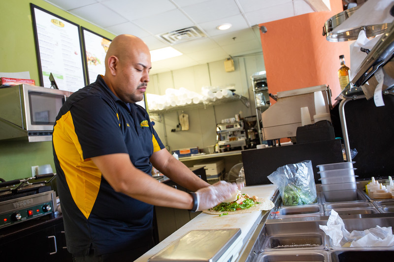 Alex Pampa makes a call in order for a customer at Health Nut Cafe located at 333 NW 5th Street in Oklahoma City. The resturaunt makes orders available to the University of Oklahoma Health Science Center through the Tapingo app service.