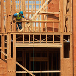 A construction worker measures an opening on the third floor of a new apartment building located on west Main Street in Oklahoma City.