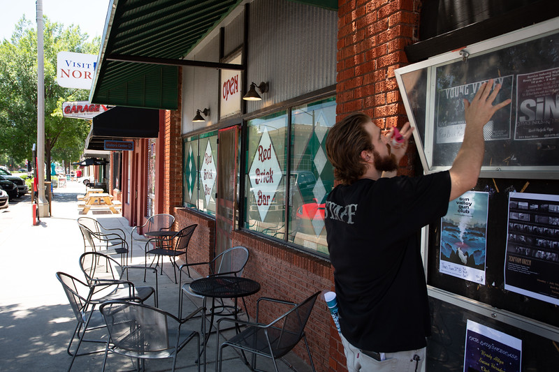 Charles Foster hangs posters for upcoming music performances outside of Red Brick Bar located in downtown Norman, OK.