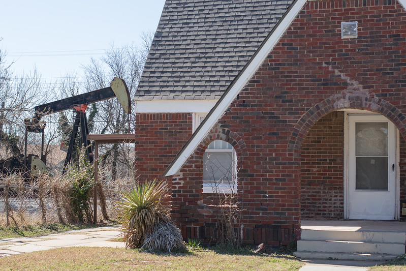 A pumpjack operated by Red Hen Oil Co located behind several homes located at 21st Street and Fonshill Ave in Oklahoma CIty.