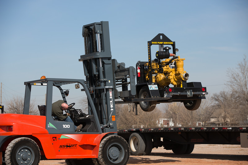 Kevin Stancil loads water pumps on a flat bed trailer at Sage Pump Service in Oklahoma City.