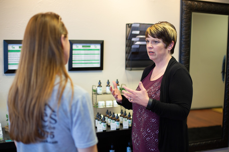 Lori Evans, co-owner of Cann-Help located at 2150A S Douglas Blvd in Midwest City, OK, helps a customer choose  CBD products.