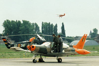 A student pilot (prom.75B) is preparing his flight with a Belgian Air Force SF-260M on the apron at Goetsenhoven, while a S-58C (reg. B14 cn: 58.850 call-sign:OT-ZKN) is parked in the background. In the air is SV-4B (code:V4, cn: 1146) practising its performance routine for the coming airshow. (Scan from slide, original taken with Canon A1 + FD35-70mm f/2.8-3.5)