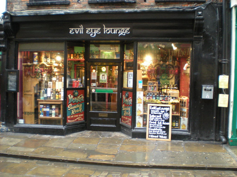 "The Evil Eye Lounge <br />  <br /> This pic was taken around 2009 the outside has been repainted and new signs are up but apart from that nothing has changed much here really  <br /> Stonegate York <br /> <br /> The amazing biggest hidden Gem in York<br /> <br />  If you like proper cocktails this is the place to Visit  <br /> <br /> Also doubles as an Internet cafe and Thai Restaurant / come off license at the front  <br /> <br /> Trust me this place is awesome and me and Liz have been to some bars that say they do cocktails but they not a shade on what they do here this place is just amazing no beers on tap though it's all bottles but they do have a decent selection of bottles even Rauchbier in bottles <br /> <br /> website:<br /> <br />  <a href=""http://www.evileyelounge.com/"">http://www.evileyelounge.com/</a>"