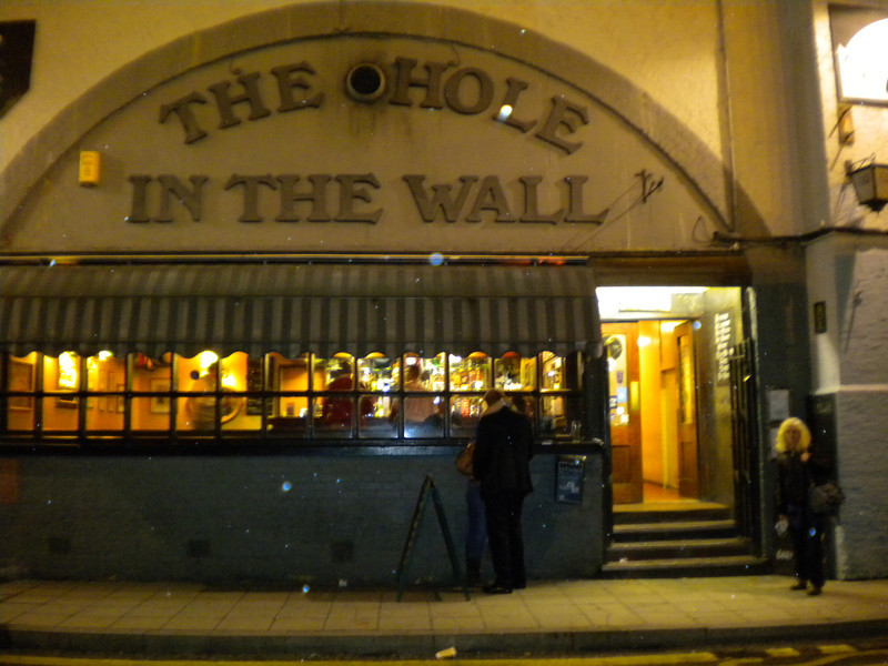 Liz <br /> <br /> Stands outside the Hole in the Wall pub <br /> <br /> 5 Mepham Street SE1 8SQ <br /> <br /> I first came here many / many years ago when i was bashing 47's a certain mr Mark Jamieson took me here between 47 moves on Waterloo - Exeter when it was NSE 47/7's <br /> and i just fell in love with the place i know that a lot of the 50 bashers used to frequent this pub in the good old days top Boozer <br /> <br /> Last time i was here was 2002 <br /> <br /> I had been Raving for the last 5 - 6 Yrs about this Place to Liz and how cool and crazy it was with the trains rattling over your head and the floor shakes etc and she wasn't to be disappointed even if the place now has music playing so you can only just hear the trains but you can feel the vibrations though ya chair <br /> <br /> Right across from Waterloo Station it's built into the Viaduct that goes into Charing X it has so i found out changed a lot since I was last here still some top beers on though and you can still here the trains rattling over the top and the Floor still vibrates as Liz felt through her chair when the trains went over the top <br /> <br /> 7 beers available<br /> <br /> the back room the ceiling is actually the arch of the Viaduct into Charing Cross
