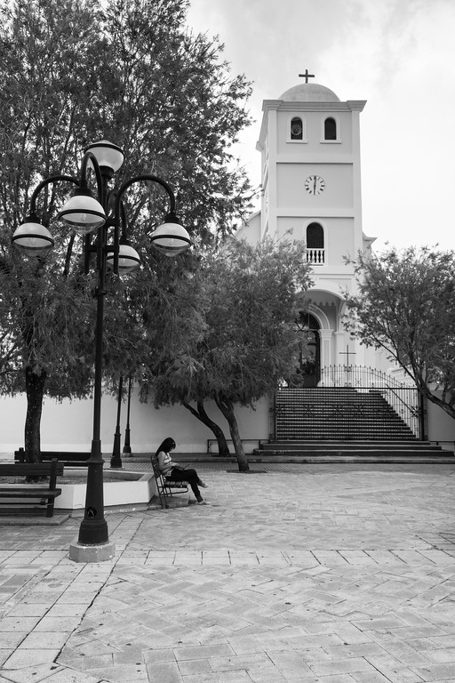 A woman relaxes in an otherwise empty town square. Lares, PR<br /> <br /> PR-090806-0130