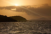 The sun escapes from the clouds on a hot and hazy morning at Culebras. In the distance, sunbeams shine on Culebrita's silhoutte. Culebra, PR<br /> <br /> PR-110725-0006