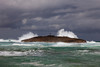 A small island with a cross on it and large waves on the north coast of Puerto Rico,  Caribbean, West Indies.
