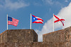 The flags of the United States, Puerto Rico and the Spanish Cross of Burgundy fly over the walls of the San Cristobal Castle in San Juan, Puerto Rico, West Indies.