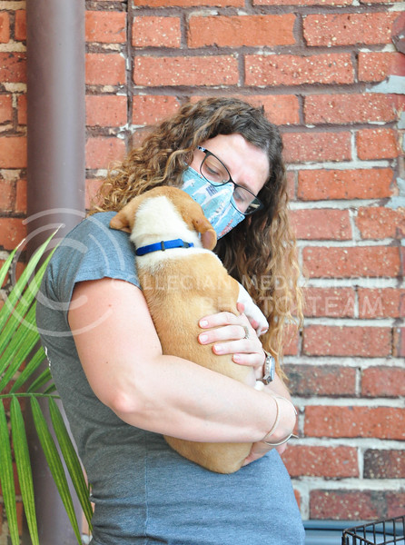 Public Hall and  Riley County Humane Society teamed up to host an adoption and fundraising event on August 5th.  A potential adopter bonds with a puppy in Public Halls back patio. (Aubrey Bolinger | Collegian Media Group)