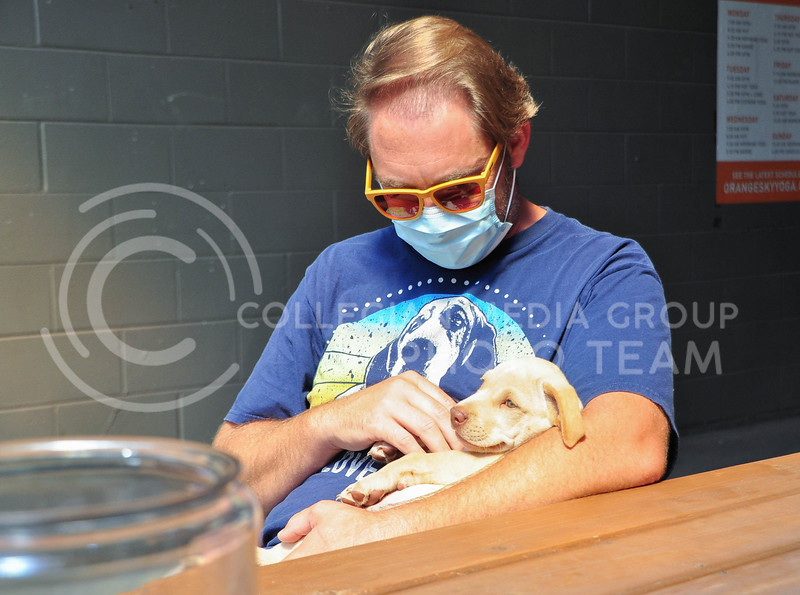Sitting on the back patio of Public Hall, a supporter of the Riley County Humane Society holds one of the available puppies. The Humaine Society was raising money at the coffee shop from 10-1 August 5th. (Aubrey Bolinger | Collegian Media Group)